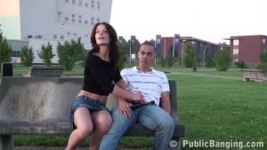 Une charmante brunette en mini jupe suce deux bites dans un parc public