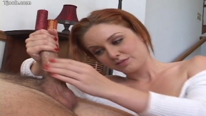 Jeune rousse joue avec une bite